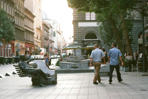 Two men look at a bench with a statue on it. (film photo: Olympus OM-2 and FujiFilm Superia 200)