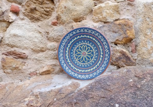 A totally random pottery plate thing on a rock wall in Pals