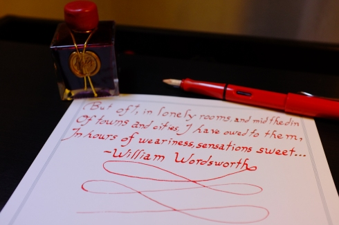 """My red Lamy Safari with a 1.5mm italic nib; a bottle of J. Herbin 1670 """"Rouge Hematite"""" ink, my personal favorite; and a Wordsworth quote on Crane & Co. triple hairline stationery."""
