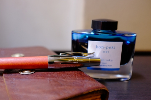 My smoothest-writing (and most treasured) pen, the Faber-Castell e-motion with pearwood; my original Bibliographica journal; and Iroshizuku kon-peki ink.