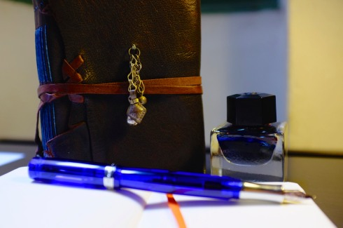"""A Kaweco """"Student"""" fountain pen in blue; one Leuchtturm1917 pocket notebook, dot grid, in orange; my Bibliographica """"Nomad"""" journal; and a bottle of the now-discontinued Caran d'Ache """"Storm"""" ink."""